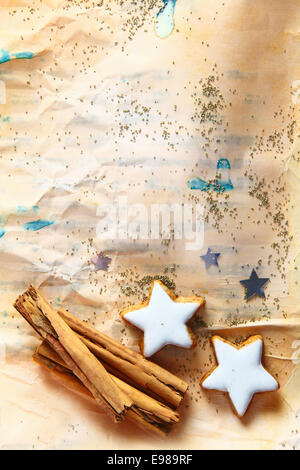 Grunge Christmas background with star-shaped cookies and stick cinnamon on aged stained crumpled paper strewn with - Stock Photo