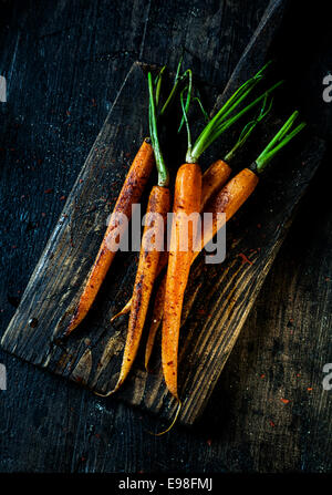 Pile of fried fresh young whole carrots ready to be eaten served on an old grungy rustic wooden board, overhead - Stock Photo