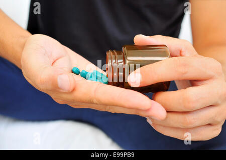 a young man with a bottle of pills in his hands - Stock Photo