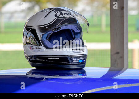 motorsport racing crash helmet resting on the roof of a race car [editorial use only ] - Stock Photo