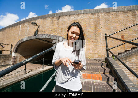 Smiling young woman using smart phone on stairs - Stock Photo