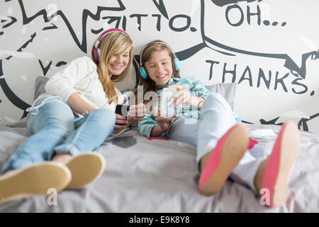 Relaxed sisters listening to music at home - Stock Photo
