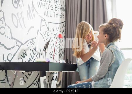 Teenage girl putting lipstick on sister at home - Stock Photo