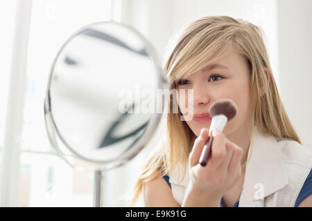 Girl applying makeup in front of mirror at home - Stockfoto