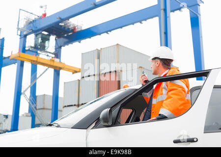 Middle-aged man using walkie-talkie while standing at car door in shipping yard - Stock Photo