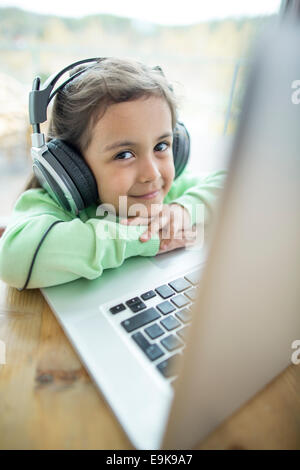 Portrait of cute girl listening to music on headphones while using laptop at home - Stock Photo
