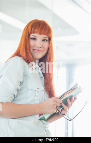 Portrait of smiling businesswoman holding files in creative office - Stock Photo