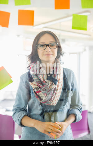 Portrait of smiling businesswoman standing by glass wall with sticky notes in office - Stock Photo