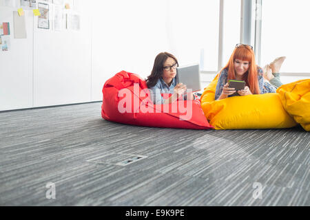 Businesswomen using digital tablets while relaxing on beanbag chairs in creative office - Stock Photo