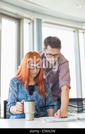 Businesspeople reading file together at desk in creative office - Stock Photo