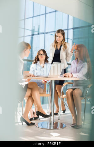 Businesswomen discussing at table in office - Stock Photo