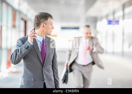 Middle aged businessman looking at colleague running in railroad station - Stock Photo
