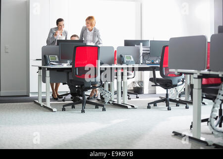 Business people having lunch while using computer in office - Stockfoto