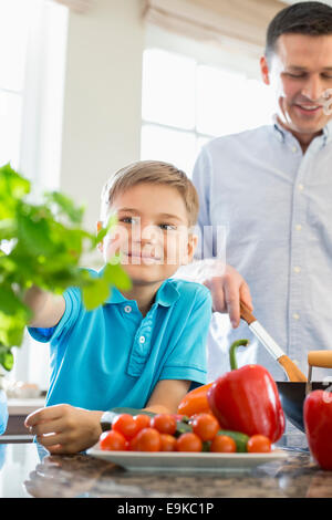 Smiling boy touching houseplant with father preparing food in kitchen - Stock Photo