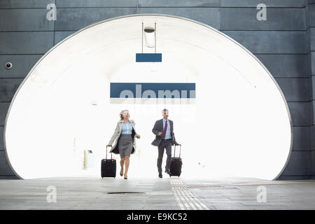 Businessman and businesswoman rushing in railroad station - Stock Photo