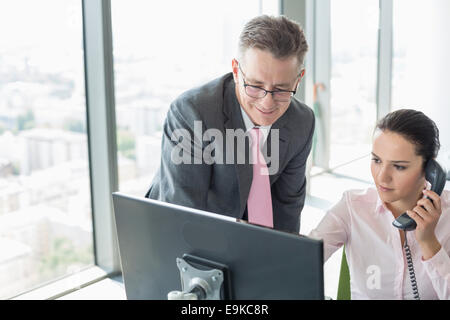 Businessman and businesswoman working together in office - Stock Photo