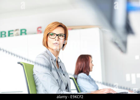 Young businesswoman working on computer with colleague in background at office - Stock Photo