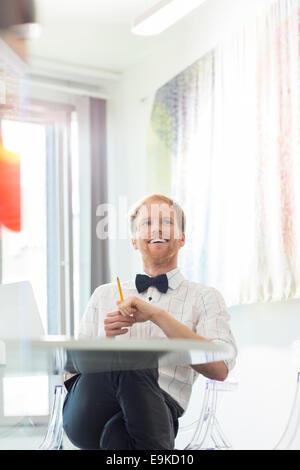 Happy businessman looking away in creative office - Stockfoto