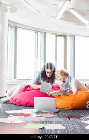 Businesswomen using tablet PC while relaxing on beanbag chairs at creative office - Stock Photo