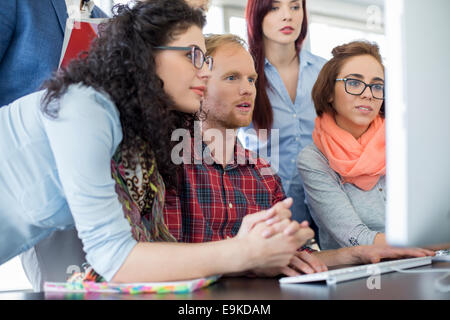 Business people working together on computer in office - Stock Photo