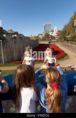 Tower of London poppies memorial - children visiting with their dolls looking at the poppies in the moat, London - Stock Photo
