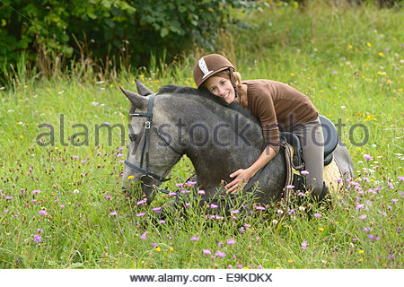 young rider on back of a lying connemara pony stock photo