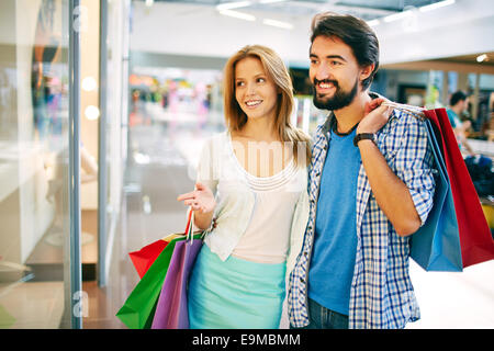 Pretty female showing her husband something in the shop window - Stock Photo