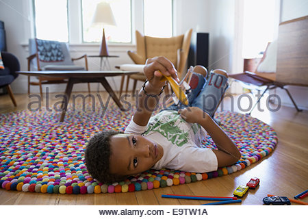 Boy playing with toy plane on rug - Stock Photo