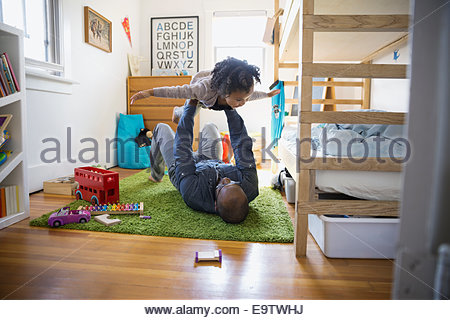Father lifting flying daughter in bedroom - Stockfoto
