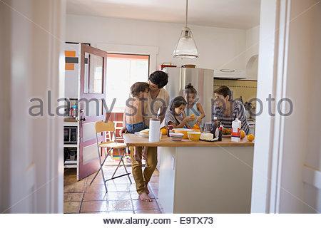 Family enjoying breakfast in kitchen - Stock Photo