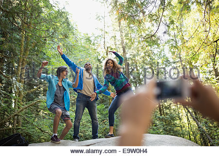 Friends playfully posing for photograph in woods - Stock Photo