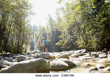 Couple standing on rock at creekside in woods - Stock Photo