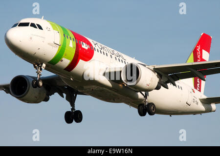 TAP Portugal Airbus A320 approaches runway 27L at London Heathrow Airport. - Stock Photo