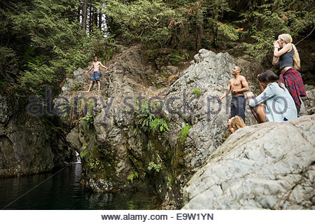 Boy preparing to jump from rocks into water - Stock Photo