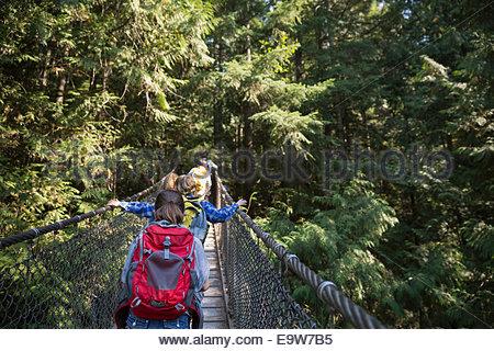 Children with backpacks crossing plank bridge in woods - Stockfoto