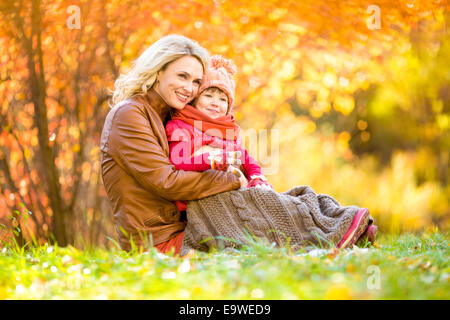Happy mother and child outdoor in autumn park - Stock Photo