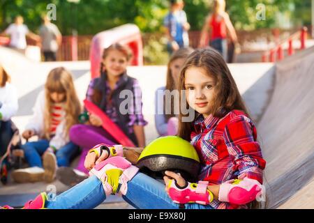 Girl holds helmet wearing in-line skates sitting - Stockfoto