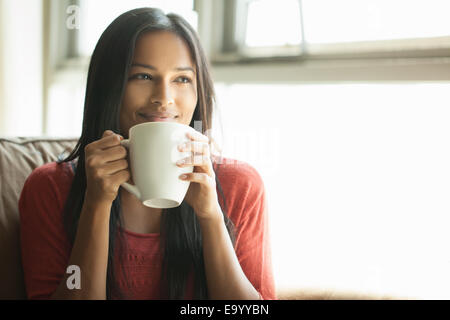 Woman having coffee at home - Stock Photo