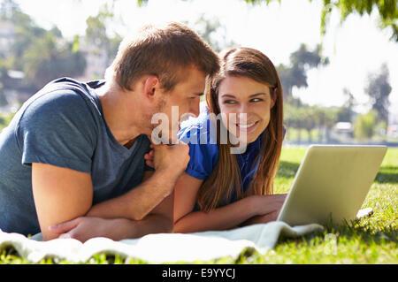 Couple using laptop in park - Stockfoto