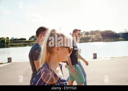 Four young friends walking along riverside - Stock Photo