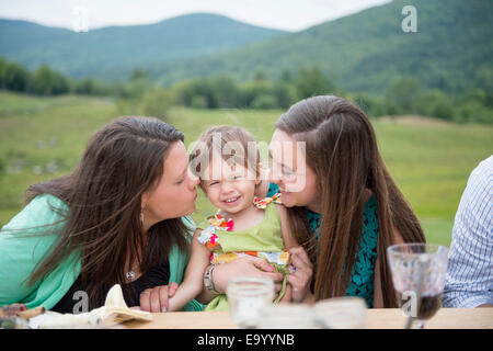 Baby girl sitting between two young women - Stock Photo