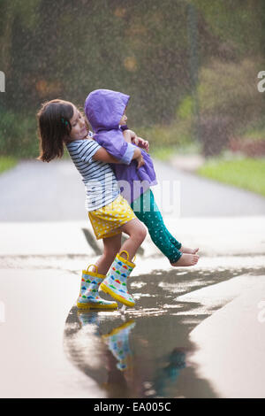 Girl carrying toddler sister through puddle on street - Stock Photo