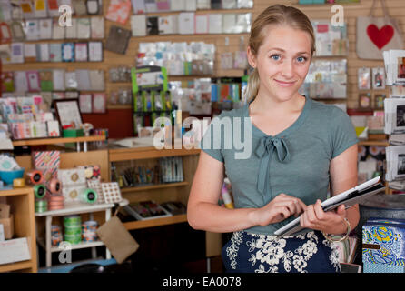 Portrait of female sales assistant using digital tablet in stationery shop - Stock Photo