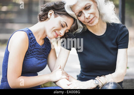 Young woman sharing tender moment with mentor - Stock Photo
