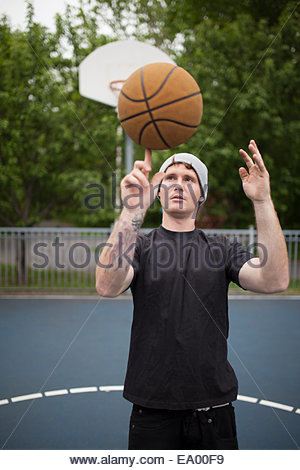 Young man balancing basketball on finger - Stock Photo