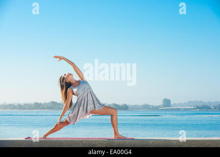 Young woman practicing yoga on pier at Pacific beach, San Diego, California, USA - Stock Photo