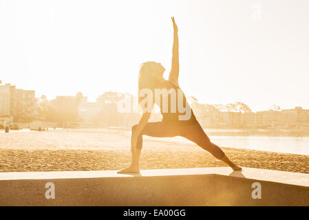 Young woman doing yoga on pier at Pacific beach at sunset, San Diego, California, USA - Stock Photo