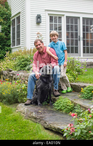 Portrait of father and son with dog - Stock Photo