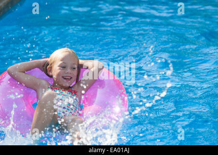 Girl lying on her back on inflatable ring in garden swimming pool - Stock Photo