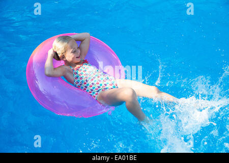 Girl lying back on inflatable ring in garden swimming pool - Stock Photo